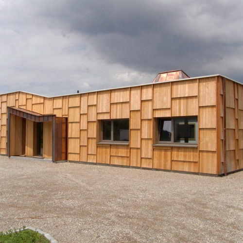 Local professionnel structure en bois orienté nord, ce qui limite les apports thermiques d'été. Bardage bois