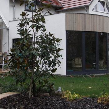 Agrandissement d'une maison individuelle, ossature bois, revêtements crépis et bois, surélévation de la salle debain