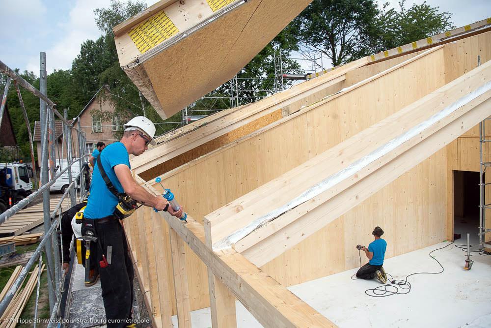 Construction d'une école en bois par des charpentiers, matériaux écologiques