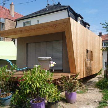 Accolée au bâtiment principal, cette extension en bois abrite une pièce à vivre, ainsi qu'une terrasse en bois partiellement couverte dans son prolongement