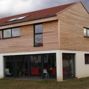 maison individuelle construction bois, grande baie vitrée, revêtement bardage bois et crépis