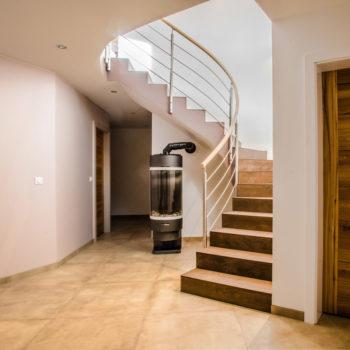 Intérieur d'une maison à ossature bois, escalier et poêle à bois