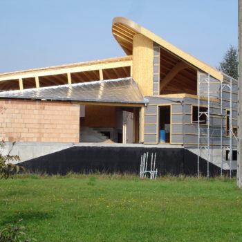 Levage d'une maison ossature charpente bois et maçonnerie, toit courbé en bois