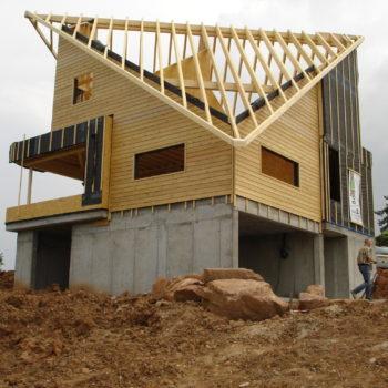 Levage d'une maison contemporaine individuelle ossature et charpente bois, poutres en bois, toit décalé