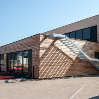 Bâtiment dédié à l'enfance, revêtement bardage bois et crépis