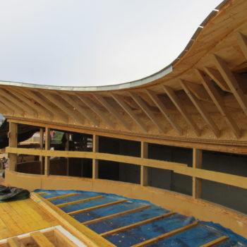 Levage d'un bâtiment en bois, toiture courbée en bois