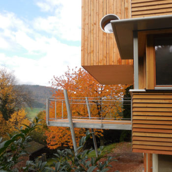 Terrasse et maison contemporaine en bois, surplombant la montagne