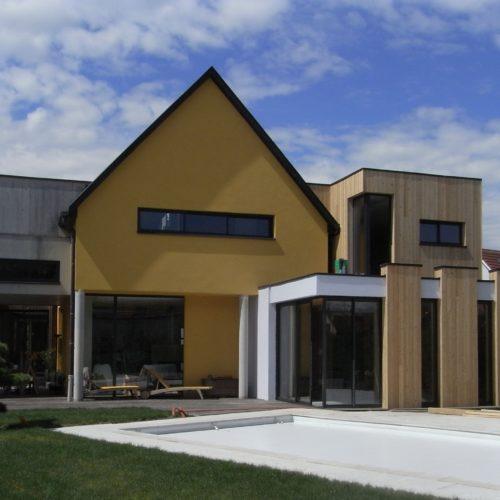 Grande extension en bois d'une maison individuelle, habillée d'un bardage bois en mélèze.