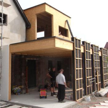 Levage d'une extension en bois d'une maison contemporaine, habillée d'un bardage bois en mélèze.