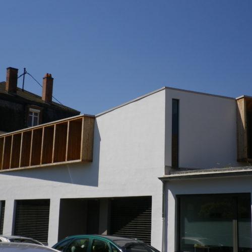 Extension et rénovation en bois d'un ancien garage, revêtement crépi et contours de fenêtres en bois