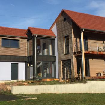 Maison individuelle contemporaine, charpente et ossature bois, terrasse en bois, revêtement enduit, verre et bardage bois, bâtiment basse consommation