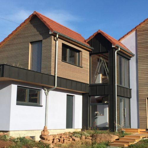 Maison contemporaine individuelle, charpente et ossature bois, bâtiment basse consommation, revêtement enduit, verre et bois