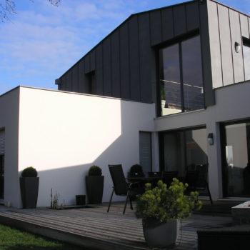 Maison contemporaine individuelle à toiture cintrée, isolant intérieur laine minérale, ossature bois