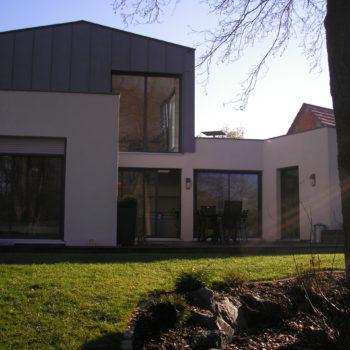 Maison contemporaine individuelle ossature et charpente bois, terrasse en bois, revêtement crépis et zinc