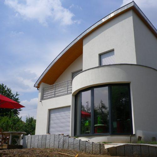 Maison individuelle contemporaine courbée, ossature et charpente bois, habillage crépis
