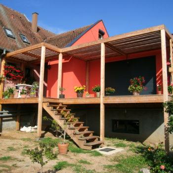 Terrasse en bois surélevée couverte accolée à une maison d'habitation