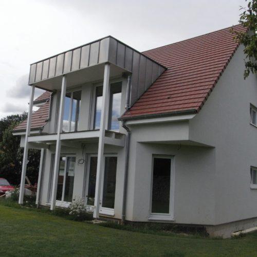 Maison contemporaine ossature et charpente bois, poutres en bois, terrasse en bois, habillage crépis blanc cassé posé sur de la fibre de bois